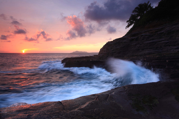 Waves crash on cliffs spitting caves explosions sunset splashing Oahu Hawaii
